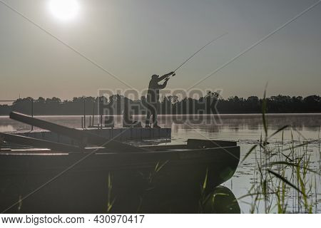Fisherman Fishing In Early Serene Morning. Man Black Silhouette Resting With Rod On River Or Lake Wi