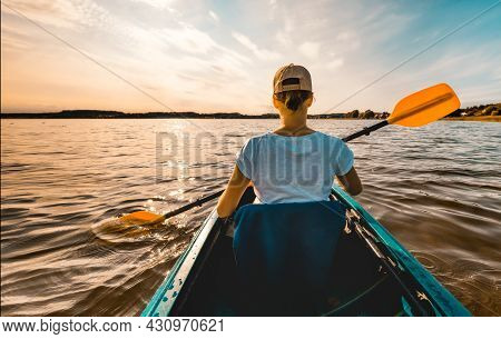 Young Girl In A Kayak Paddling On The Lake At Sunset - Rear View From Behind Her Back