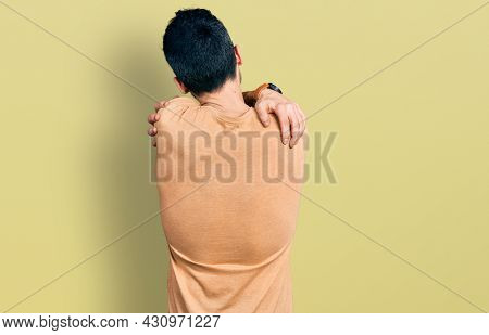 Hispanic man with beard wearing casual t shirt hugging oneself happy and positive from backwards. self love and self care