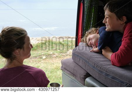 Mother And Children Looking At Each Other Sitting In Their Campervan With The Sea In The Background.