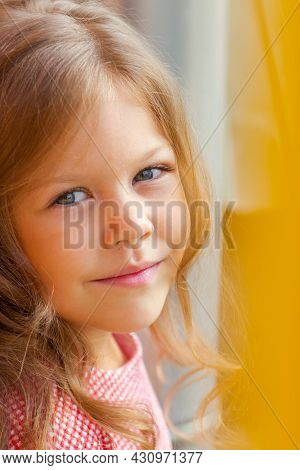Portrait Of Smiling Caucasian Little Girl Of Five Years Old Looking At Camera
