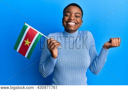 Young african american woman holding suriname flag screaming proud, celebrating victory and success very excited with raised arm