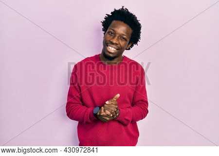 Young african american man wearing casual clothes with hands together and crossed fingers smiling relaxed and cheerful. success and optimistic