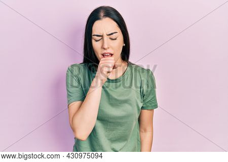 Beautiful woman with blue eyes wearing casual t shirt feeling unwell and coughing as symptom for cold or bronchitis. health care concept.