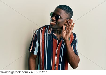 Young african american man wearing casual clothes and sunglasses smiling with hand over ear listening and hearing to rumor or gossip. deafness concept.