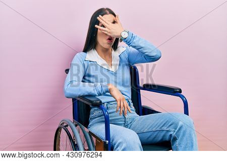 Beautiful woman with blue eyes sitting on wheelchair peeking in shock covering face and eyes with hand, looking through fingers with embarrassed expression.