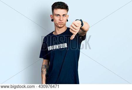 Young caucasian boy with ears dilation wearing volunteer t shirt looking unhappy and angry showing rejection and negative with thumbs down gesture. bad expression.