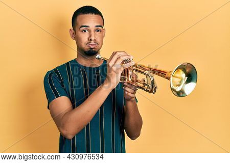 Young african american man playing trumpet puffing cheeks with funny face. mouth inflated with air, catching air.