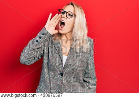 Beautiful caucasian blonde woman wearing business jacket and glasses shouting and screaming loud to side with hand on mouth. communication concept.