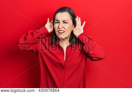 Middle age hispanic woman wearing casual clothes trying to hear both hands on ear gesture, curious for gossip. hearing problem, deaf