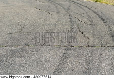 Gray Asphalt With Black Tire Tracks. An Old Country Road With Cracks. Curved Wheel Tracks In A Bend
