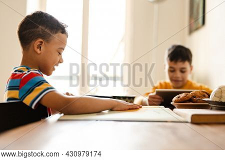 Two preteen african boys brothers sitting at the table at home doing homework