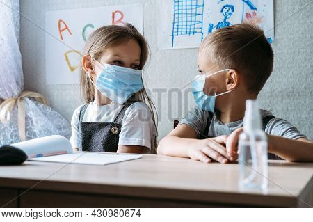 Back To School Safety. Schoolkids Wearing Masks And Using Antiseptic In Classroom At School. Hildren