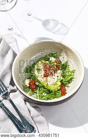 Avocado and stracciatella cheese salad. Fancy dinning with Italian salad bowl on white table with simple contemporary decor. Sunlight and harsh shadow still life. Avocado, cheese and tomato salad