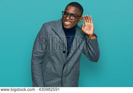 Young african american man wearing business clothes and glasses smiling with hand over ear listening an hearing to rumor or gossip. deafness concept.