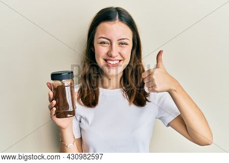 Young brunette woman holding soluble coffee smiling happy and positive, thumb up doing excellent and approval sign