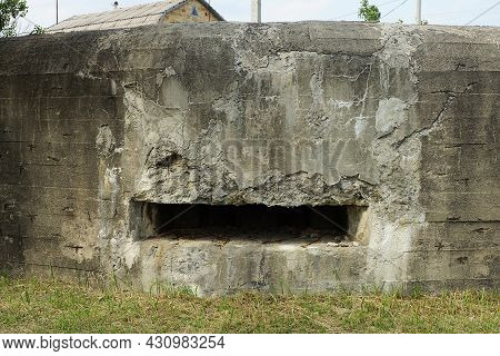 The Wall Of A Gray Old Concrete Historical Bunker With An Embrasure On The Street In The Green Grass