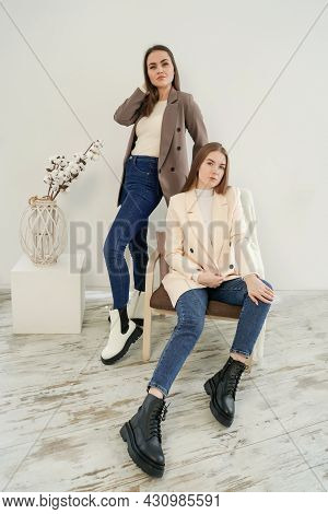 Two Young Women Wearing Blazers On White.