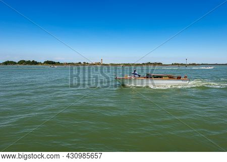 Venice, Italy - June 2, 2021: White And Wooden Water Taxi In Motion In The Venice Lagoon In Front Of