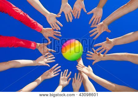 Several hands reaching out together in a circle for volley ball against blue sky poster