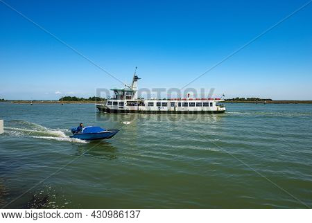 Venice, Italy - June 2, 2021: Ferry Boat And A Small Motorboat In Motion In The Venice Lagoon In Fro