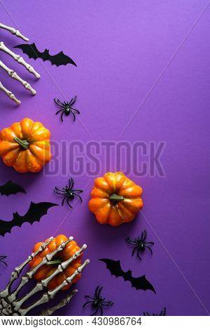 Flat Lay Halloween Decorations, Pumpkins, Bats, Spiders On Purple Background. Happy Halloween Holida