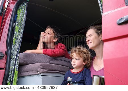 Mother And Children Sitting On The Side Of Their Campervan On Their Summer Holiday.