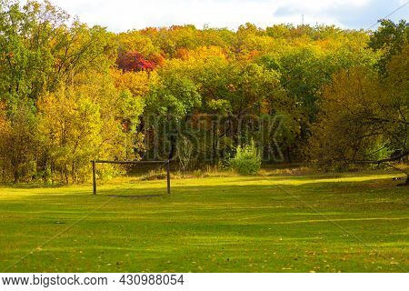 Autumn Landscape Of A Glade Of Green Lawn With Sunbeams In A City Park.