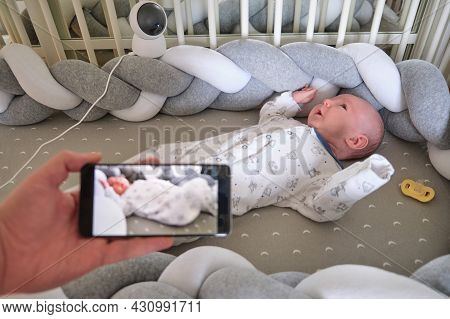 Monitoring Of A Newborn Baby In A Crib Through A Home Security Camera Online And The Internet In A M