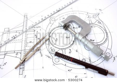 Micrometer compass ruler and pencil on blueprint