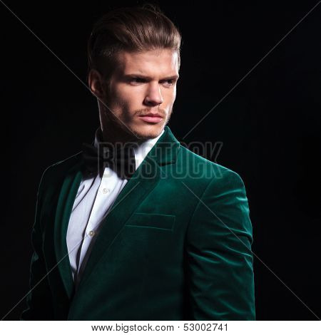 side view of a serious young man in a green velvet suit looking away from the camera on black background