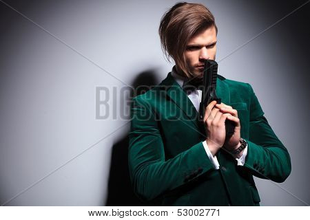 elegant assasin praying with his gun in his hands on gray background