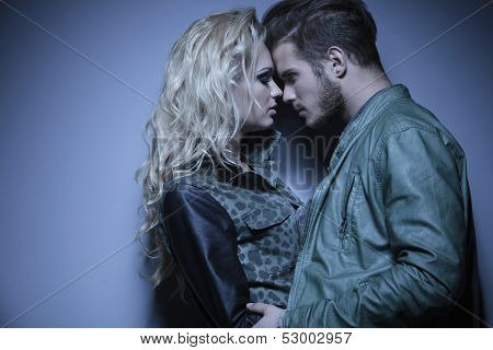 young embraced fashion couple standing face to face