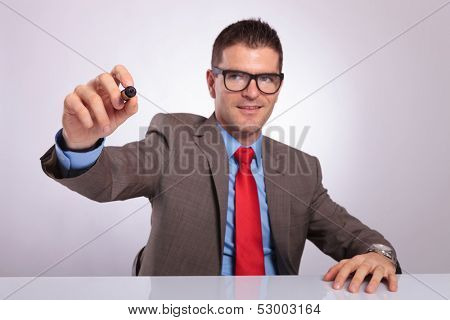 young business man sitting at his desk and writing with a marker on an imaginary screen. on a gray background