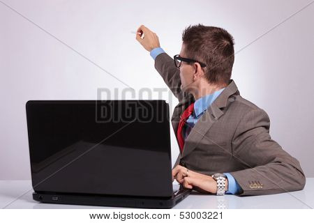 young business man sitting at laptop and writing on an imaginary screen behind him. on a gray background