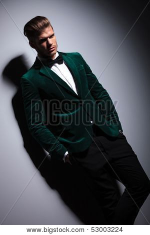 man in green suit with bow tie looks at the camera on gray background