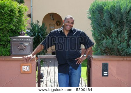 Happy African American Man In Front Of His House