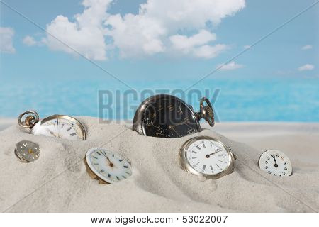 Several antique pocket watches and clocks lying in the beach sand