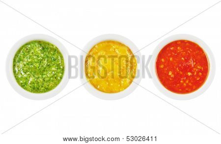 Colorful green, yellow and red spicy sauces in bowls isolated on white poster