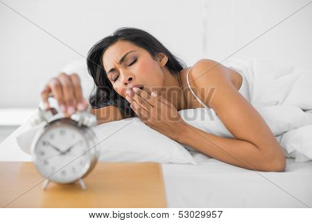 Cute yawning woman lying in her bed while turning off the alarm clock in bright bedroom