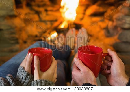 Close-up of hands holding red coffee cups in front of lit fireplace