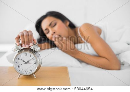Lovely yawning woman turning off the retro alarm clock lying in her bed