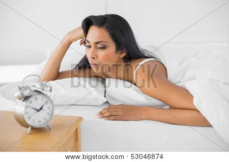 Exhausted young woman lying in her bed in bright bedroom