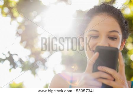 Happy brunette woman texting with her smartphone in a park