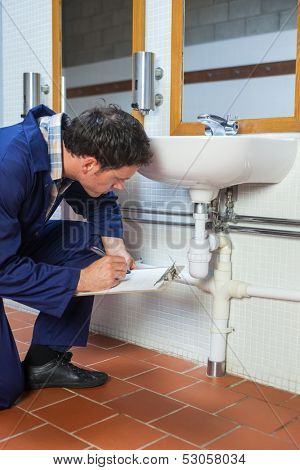 Handsome plumber inspecting sink holding clipboard in public bathroom