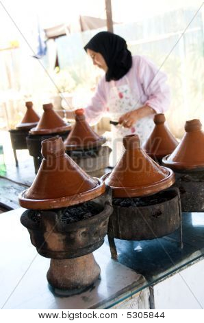 Muslim Woman Cooking Food In Tagine Morocco