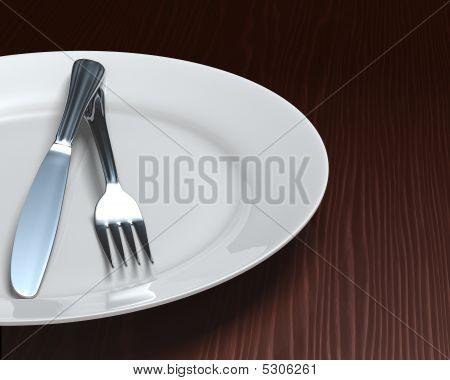 Clean Plate & Cutlery On Dark Woodgrain Table