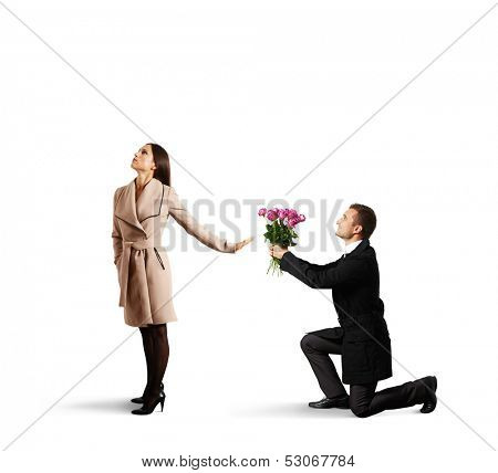 young beautiful woman rejecting man with flowers. isolated on white background