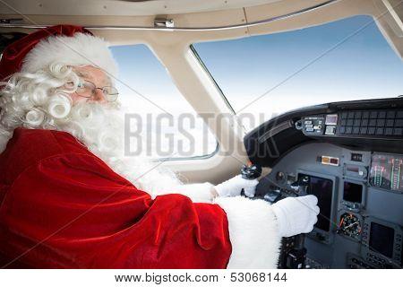 Portrait of man in Santa costume holding control wheel in cockpit of private jet