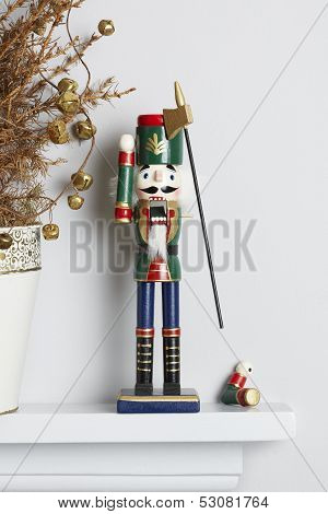 Christmas nutcracker solider broken on mantle piece with decorated dead pine tree. Unhappy xmas concept poster